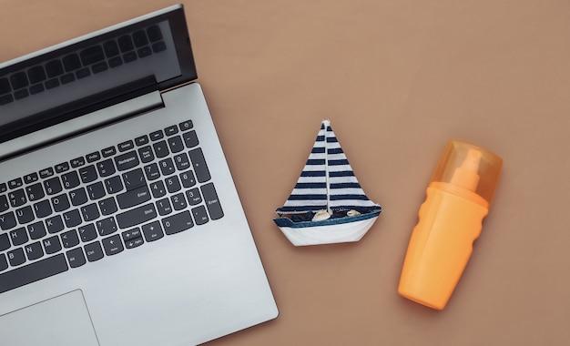 Planejando viagens. laptop e veleiro, frasco de protetor solar em um fundo marrom. vista do topo. postura plana