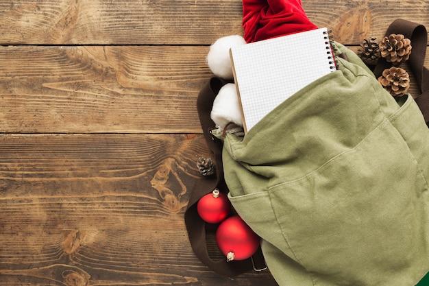 Planejando viagens. mochila vintage com caderno em branco, chapéu de papai noel e decorações festival de natal na mesa de madeira.