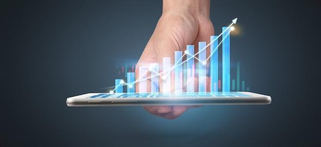 Planeje o crescimento do gráfico e o aumento dos indicadores positivos do gráfico em seu negócio, tablet na mão