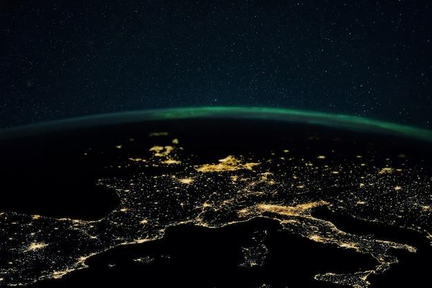 Planeta terra à noite com as luzes das cidades da megalópole à noite e as luzes do norte. europa e as cidades da itália, frança, espanha e alemanha, vista do espaço.