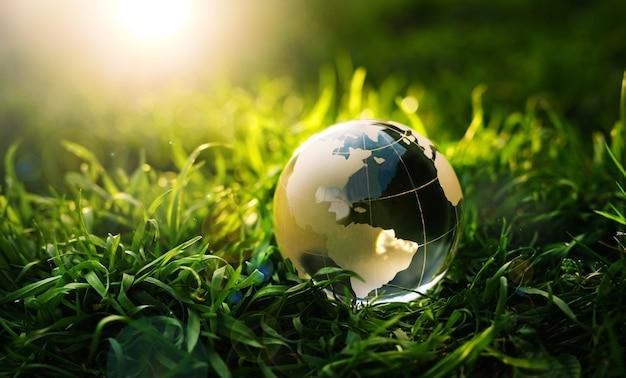 Planeta terra de cristal na grama verde ao pôr do sol conceito ambiental e do dia da terra