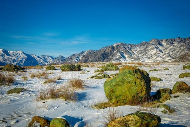 Planície coberta de neve entre as montanhas contra o céu azul em um dia ensolarado de inverno