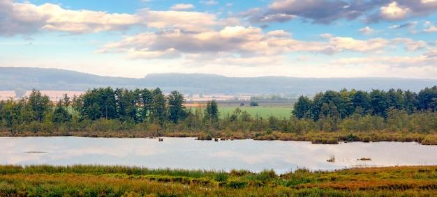 Planície com rio e árvores na margem do rio sob o céu com nuvens pitorescas no outono
