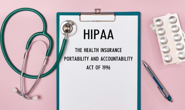 Planilha com a inscrição hipaa lei de responsabilidade e portabilidade de seguro saúde de 1996, estetoscópio e pílulas, vista superior