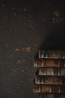 Plano antiquado com uma pilha de livros antigos encadernados em couro contra uma parede escura