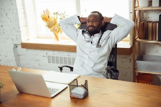 Plano aproximado de médico afro-americano para paciente que trabalha em gabinete