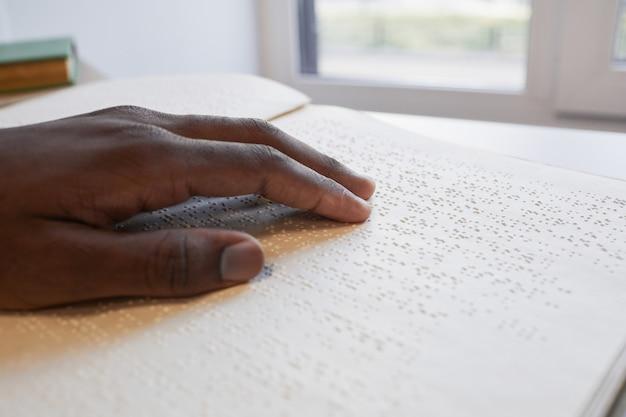 Plano aproximado de uma mão afroamericana lendo livro em braille para o espaço da cópia cega