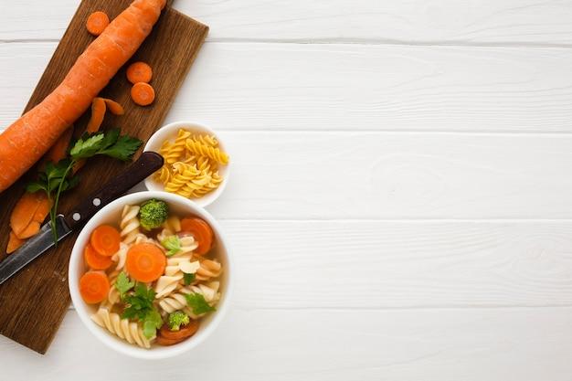 Plano colocar brócolis cenouras e fusilli em tigela com cenoura na tábua com espaço de cópia