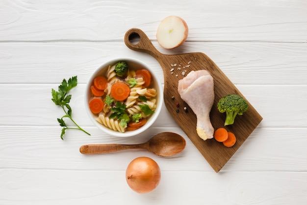 Plano colocar brócolis cenouras e fusilli em tigela com coxa de frango na tábua