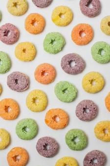 Plano colocar cereais circulares coloridos sobre fundo branco