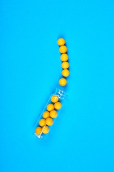 Plano colocar sobrecarga de pílulas amarelas em frasco de vidro sobre fundo azul