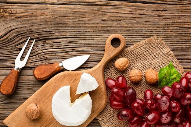 Plano colocar uvas camembert e nozes na tábua de madeira com utensílios