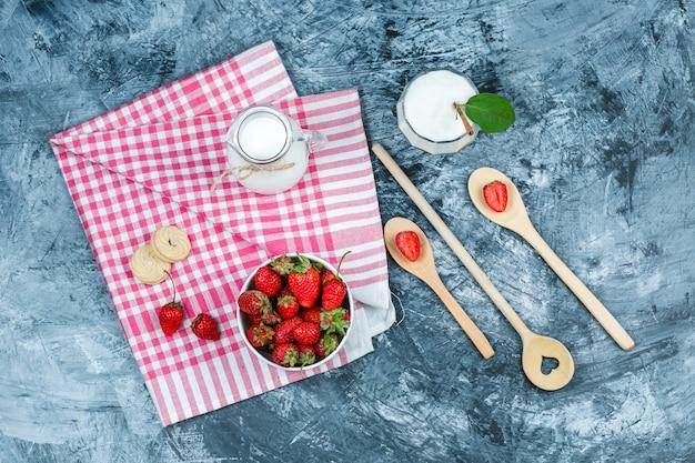 Plano coloque uma tigela de morangos e um jarro de leite em uma toalha vermelha de algodão-tecido com colheres de madeira e uma tigela de vidro de iogurte na superfície de mármore azul escuro. horizontal