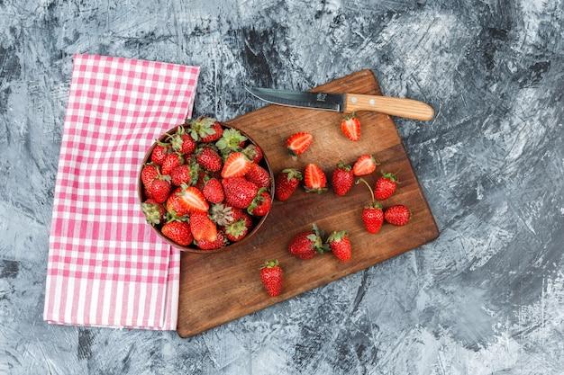 Plano coloque uma tigela de morangos e uma faca na tábua de madeira com toalha de mesa riscada vermelha na superfície de mármore azul escuro. horizontal