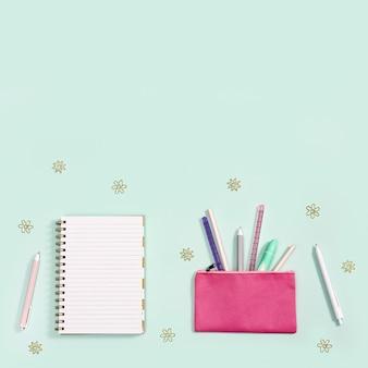Plano com material de escritório, caderno, canetas, lápis, régua, canetas hidrográficas, marcadores e clipes de papel