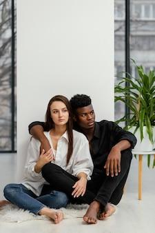 Plano completo de casal interracial sentado