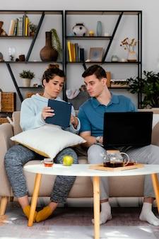 Plano completo de homem e mulher olhando para um tablet