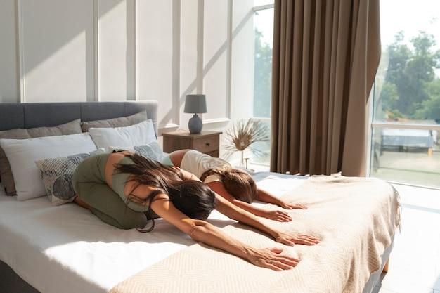 Plano completo de mulher e criança se espreguiçando na cama