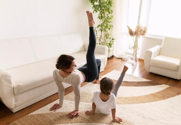 Plano completo de mulher e garota fazendo exercícios em casa