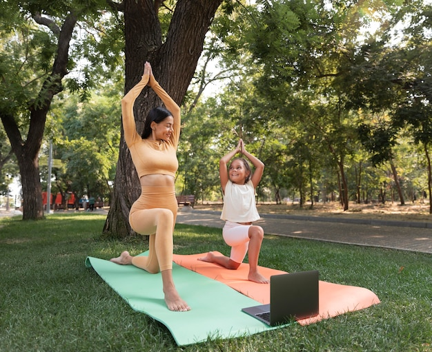 Plano completo de mulher e garota meditando do lado de fora