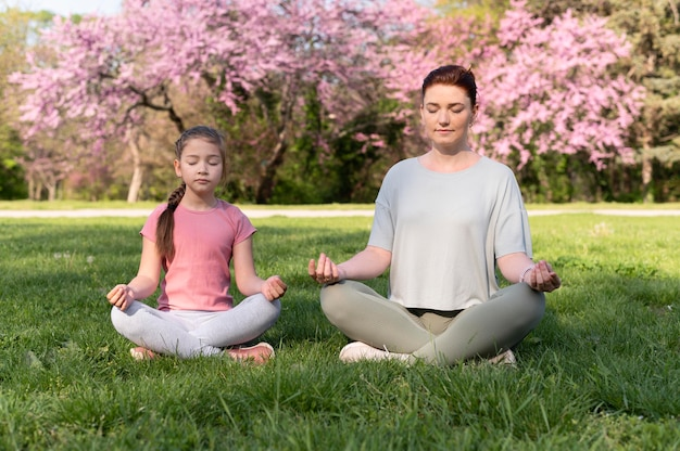 Plano completo de mulher e garota meditando