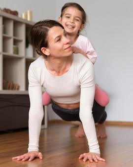 Plano completo de mulher e garota se exercitando juntas