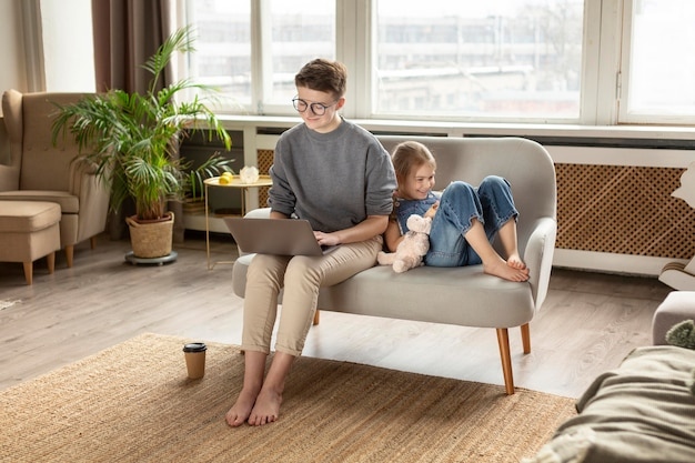 Plano completo de pai e filho no sofá