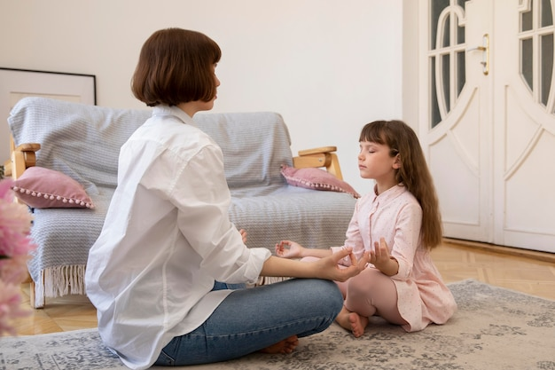 Plano completo, mãe e filha meditando juntas
