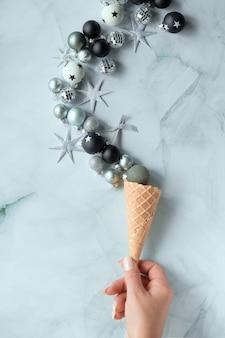 Plano criativo de natal ou ano novo. mão segura uma bola preta. casquinha de sorvete com várias decorações de natal