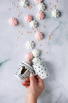 Plano criativo deitar com a mão segurando xícaras de café expresso e marshmallows na mesa de mármore.