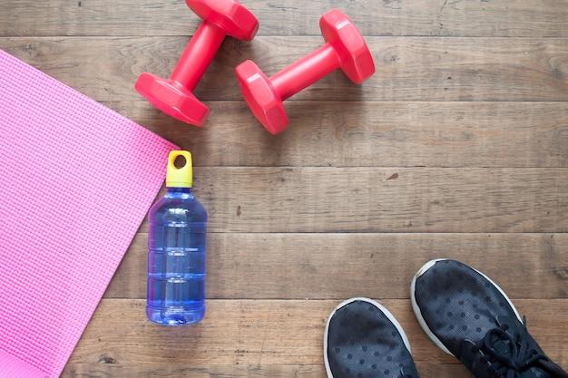 Plano criativo leigos do conceito de treino. equipamento de fitness, garrafa de água e sapatas do esporte no assoalho de madeira