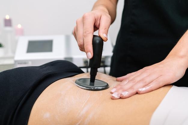 Plano curto de esteticista dando tratamento de radiofrequência a uma mulher no estômago que delineia e estimula a função celular saudável