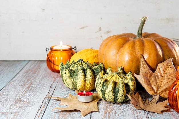 Plano de ação de graças, composição com abóboras, folhas secas de outono, velas em fundo de madeira. férias de outono, colheita de abóbora. legumes sazonais.
