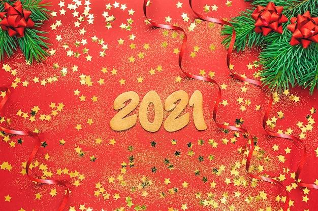 Plano de ano novo com 2021 números dourados, confetes e galhos de árvores