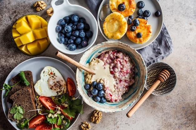 Plano de café da manhã deitado. farinha de aveia, panquecas de queijo cottage com frutas e ovo frito com salada no escuro.