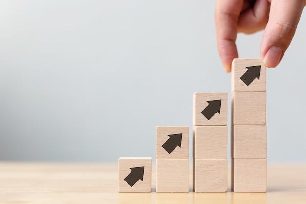 Plano de carreira de escada para o conceito de processo de sucesso de crescimento de negócios. mão organizando o empilhamento de blocos de madeira como escada com seta para cima