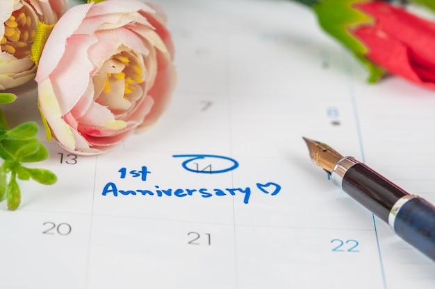 Plano de celebração de aniversário palavra no calendário com flor e caneta