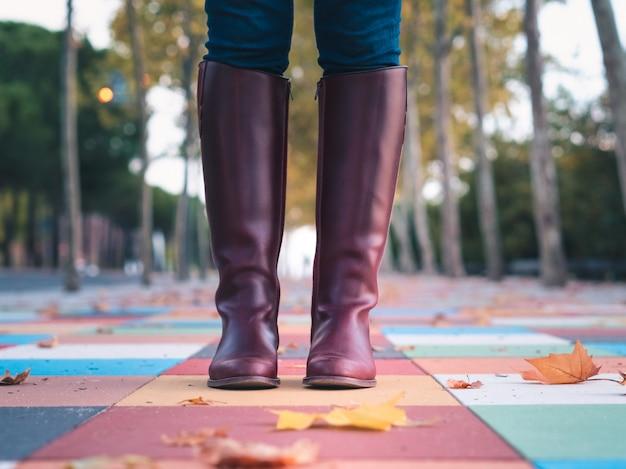 Plano de close-up de botas femininas em um belo piso de quadrados coloridos com folhas de outono