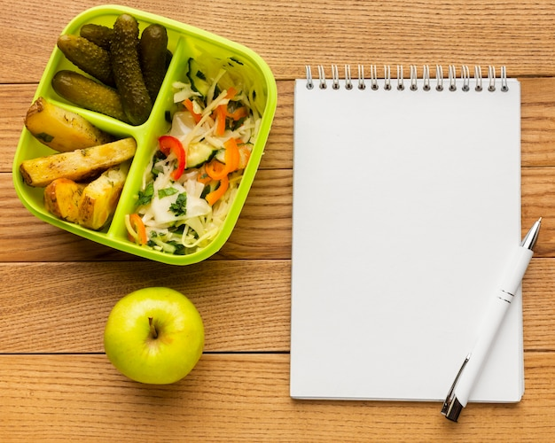 Plano de composição de refeição saborosa com caderno vazio