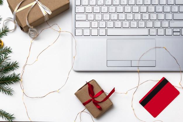 Plano de compras online de natal leigos. um laptop aberto, um cartão de crédito, caixas de presente amarradas com uma fita vermelha, ramos de pinheiro verdes, guirlandas de estrelas