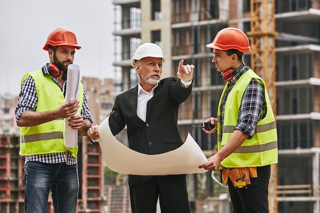 Plano de construção do engenheiro principal com roupa formal e capacete branco, segurando um esboço de