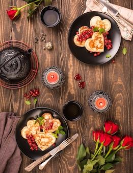 Plano de dia dos namorados com deliciosas panquecas em forma de coração, chá verde, bule preto, velas e rosas. cartão do conceito de dia dos namorados. vista do topo