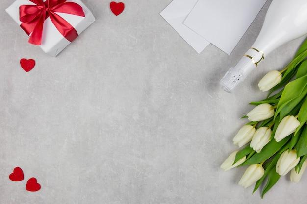 Plano de dia dos namorados deitado com champanhe, caixa de presente, corações vermelhos e buquê de flores de tulipas brancas no concreto claro.