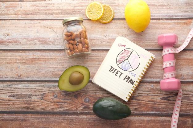 Plano de dieta com maçã e halteres na mesa de madeira