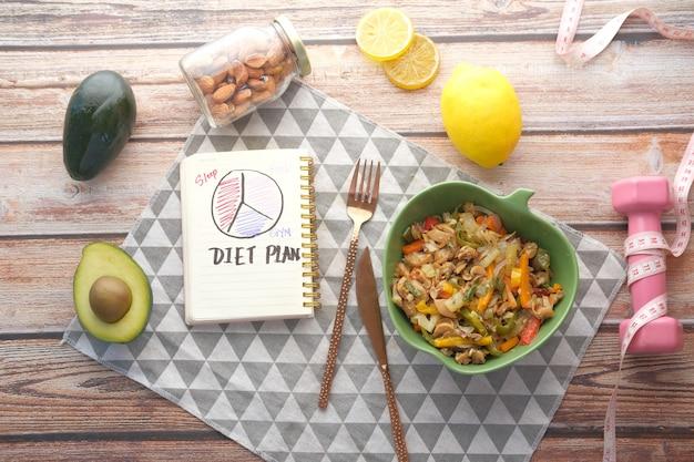Plano de dieta com refeição saudável e halteres na mesa de madeira
