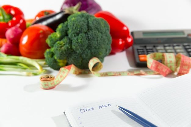 Plano de dieta e composição de vegetais maduros. close up do local de trabalho do médico nutricionista. nutrição vegetariana, comida para perder peso. ingredientes orgânicos para emagrecer