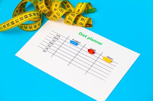 Plano de dieta e comprimidos de perda de peso em azul.