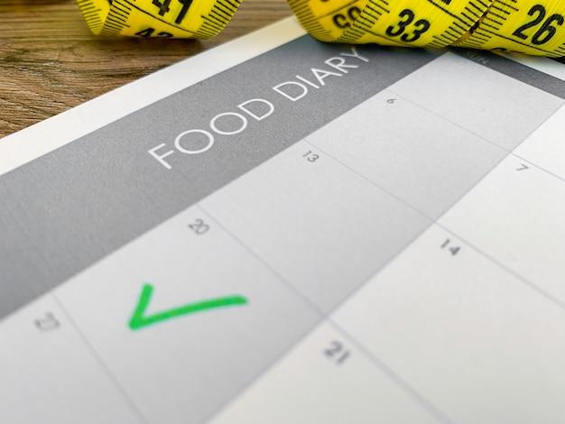 Plano de dieta . fita métrica e plano de dieta em fundo de madeira