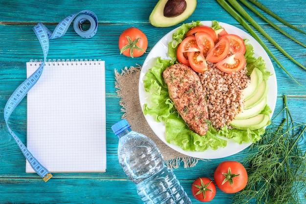 Plano de dieta, menu ou programa, fita métrica, água, almoço de peito de frango, trigo sarraceno, tomate sobre fundo azul.