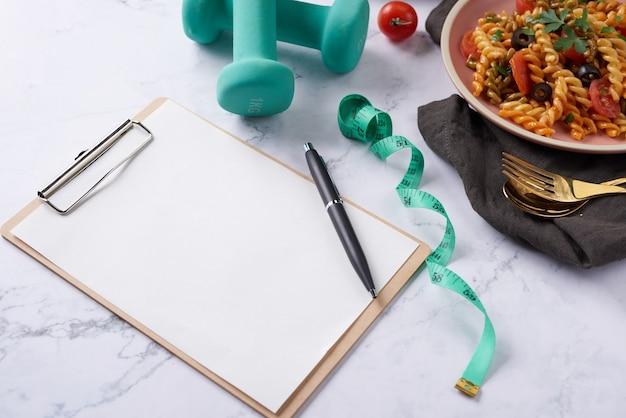 Plano de dieta, menu ou programa, fita métrica, água, halteres e alimentos dietéticos, vista de cima.